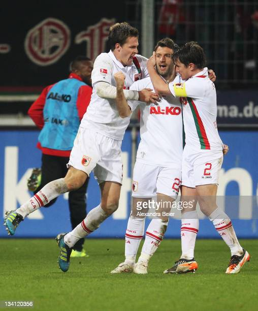 Sebastian Langkamp Edmond Kapllani and Paul Verhaegh of Augsburg celebrate Kapllani's first goal during the Bundesliga match between FC Augsburg and...