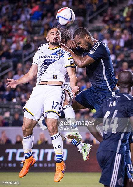 Sebastian Lietget of Los Angeles Galaxy heads the ball in front of Alan Gordon of Los Angeles Galaxy and Kendall Waston of Vancouver FC during the...