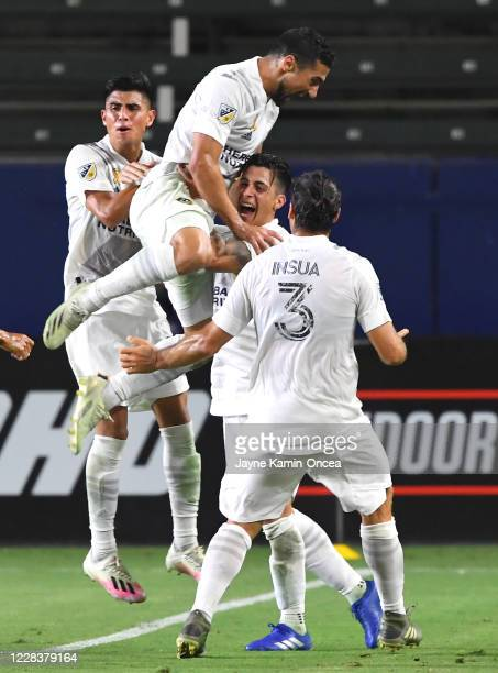 Sebastian Lletget leaps into the arms of Cristian Pavon as Joe Corona, Jonathan dos Santos and Emiliano Insua of the Los Angeles Galaxy join in to...