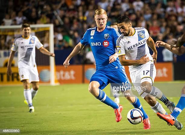 Sebastian Lletget of Los Angeles Galaxy battles Calum Mallace of Montreal Impact during Los Angeles Galaxy's MLS match against Montreal Impact at the...