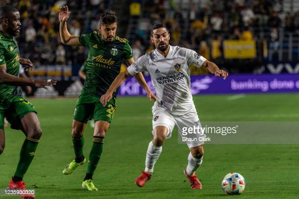 Sebastian Lletget of Los Angeles Galaxy battles Jose van Rankin of Portland Timbers during the game at the Dignity Health Sports Park on October 16,...