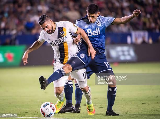 Sebastian Lletget of Los Angeles Galaxy battles Matias Laba of Vancouver Whitecaps during Los Angeles Galaxy's MLS match against Vancouver Whitecaps...