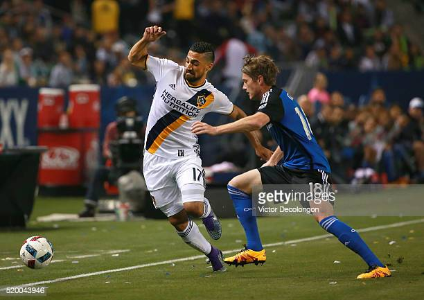 Sebastian Lletget of the Los Angeles Galaxy and Kip Colvey of the San Jose Earthquakes vie for the ball near the touchline during the first half of...