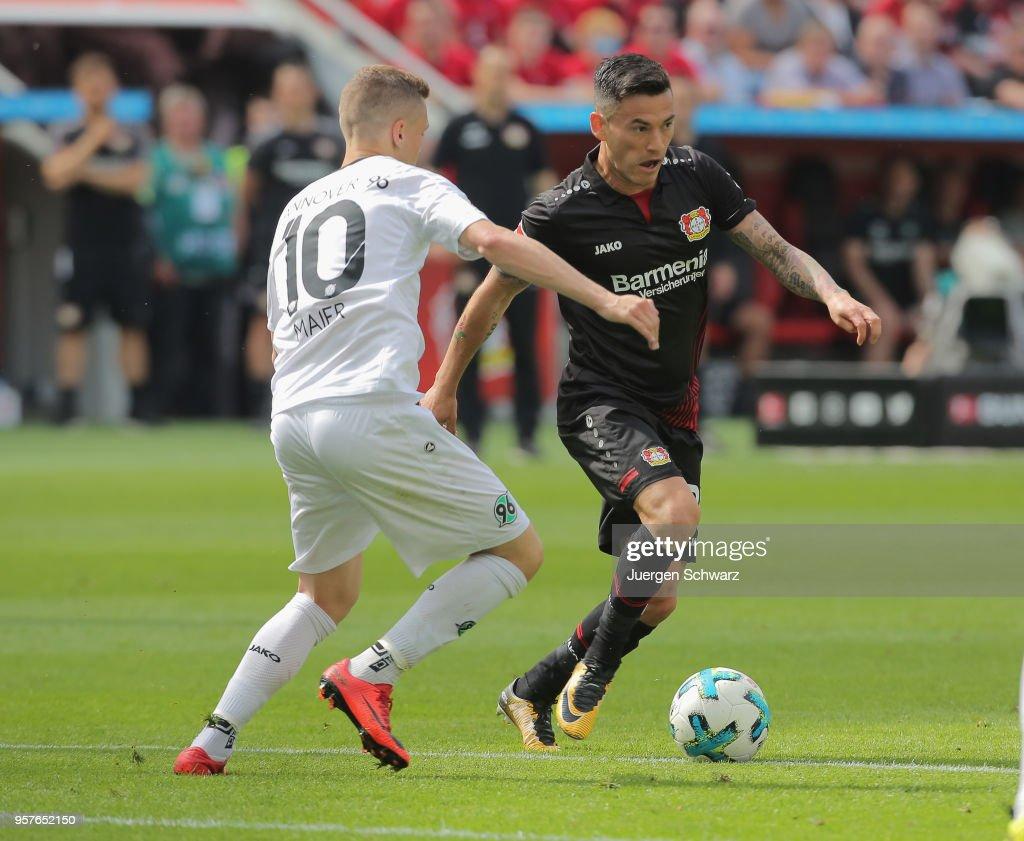 Sebastian Maier of Hannover (L) tackles Charles Aranguiz of Leverkusen during the Bundesliga match between Bayer 04 Leverkusen and Hannover 96 at BayArena on May 12, 2018 in Leverkusen, Germany.