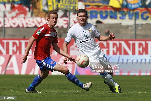 Sebastian Mitterhuber of Unterhaching battles for the ball with Ken Reichel of Braunschweig during the Third League match between SpVgg Unterhaching...