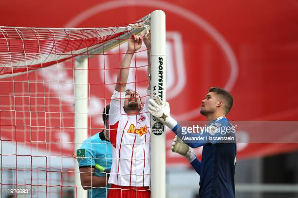 Sebastian Nachreiner of Regensburg fix the goal net with his team mate Keeper Alexander Meyer and assistent referee Philipp Hüwe during the Second...