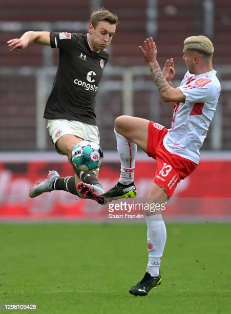 Sebastian Ohlsson of FC St. Pauli challenges for the high ball with Erik Wekesser of Jahn Regensburg during the Second Bundesliga match between FC...