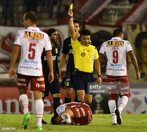 Sebastian Perez of Atletico Nacional is issued a yellow card by referee Patricio Polic during a first leg match between Huracan and Atletico Nacional...