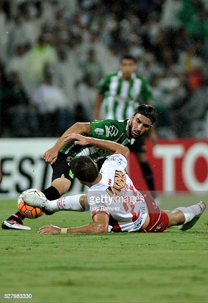 Sebastian Perez of Atletico Nacional vies for the ball with Martin Nervo of Huracan during a second leg match between Atletico Nacional and Huracan...