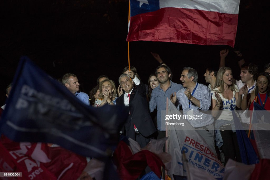Sebastian Pinera, Chile's president-elect, center, waves a Chilean flag at the National Renewal party headquarters after the second round presidential general elections in Santiago, Chile, on Sunday, Dec. 17, 2017. Pinera swept to victory in the run-off of Chile's presidential election, winning by a wider than expected margin, after pledging to reverse four years of sluggish economic growth. Photographer: Cristobal Olivares/Bloomberg via Getty Images