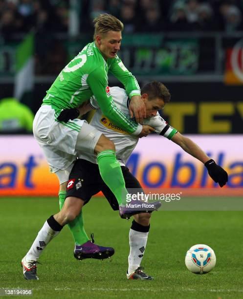 Sebastian Polter of Wolfsburg and Filip Daems of Moenchengladbach battle for the ball during the Bundesliga match between VfL Wolfsburg and Borussia...