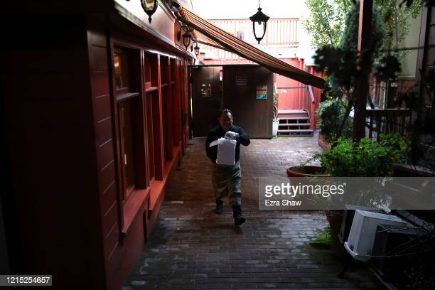 Sebastian Pool a worker at Sociale carries a take out order to the curb March 27 2020 in San Francisco California Sociale is working with a reduced...