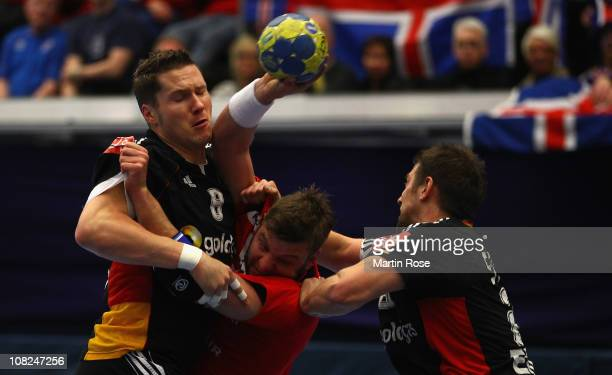 Sebastian Preiss and Michael Haass of Germany are challenged by Robert Gunnarsson of Iceland during the Men's Handball World Championship main round...