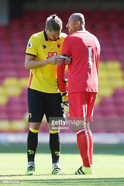 Sebastian Prodl of Watford puts the captain's armband on team mate Heurelho Gomes during the preseason friendly match between Watford and Lorient at...