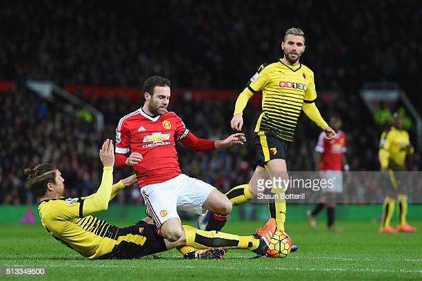 Sebastian Prodl of Watford slides in to tackle Juan Mata of Manchester United during the Barclays Premier League match between Manchester United and...