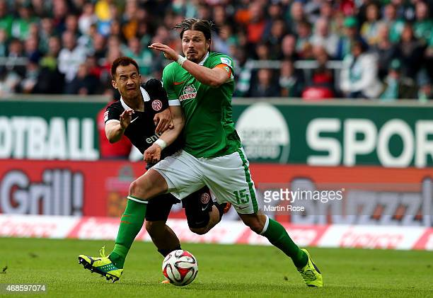 Sebastian Proedl of Bremen and Shinji Okazaki of Mainz battle for the ball during the Bundesliga match between SV Werder Bremen and 1 FSV Mainz 05 at...