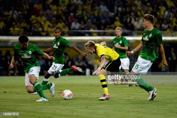 Sebastian Proedl of Bremen challenges Marco Reus of Dortmund during the Bundesliga match between Borussia Dortmund and Werder Bremen at Signal Iduna...
