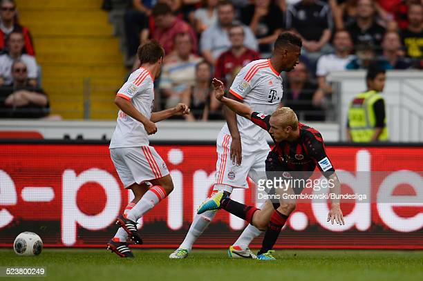 Sebastian Rode of Eintracht Frankfurt is challenged by Philipp Lahm and Jerome Boateng of Bayern Muenchen during the Bundesliga match between...