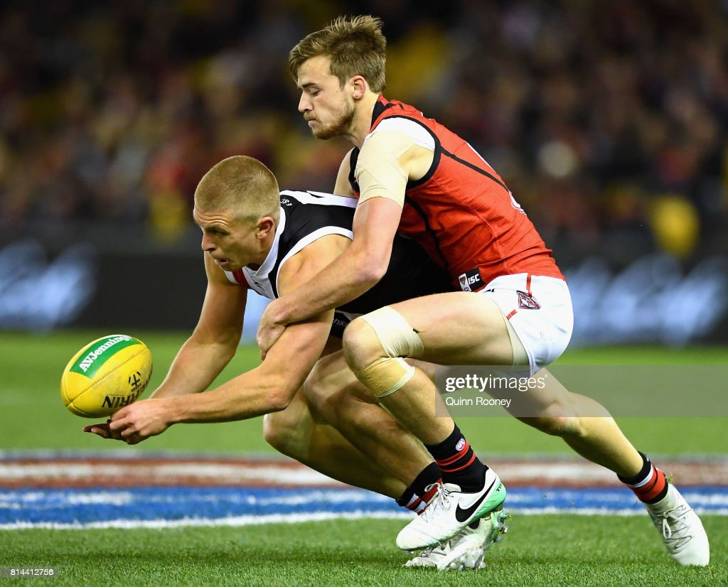 Sebastian Ross of the Saints handballs whilst being tackled by Martin Gleeson of the Bombers during the round 17 AFL match between the St Kilda Saints and the Essendon Bombers at Etihad Stadium on July 14, 2017 in Melbourne, Australia.