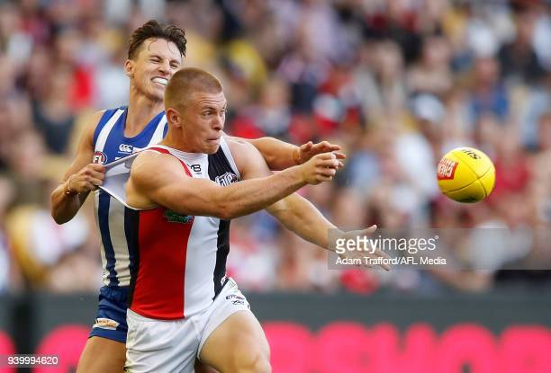 Sebastian Ross of the Saints handpasses the ball ahead of Ben Jacobs of the Kangaroos during the 2018 AFL round 02 Good Friday Kick for the Kids...
