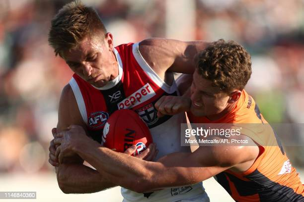 Sebastian Ross of the Saints Is tackled by Jacob Hopper of the Giants during the round seven AFL match between the Greater Western Sydney Giants and...
