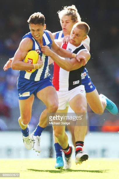 Sebastian Ross of the Saints tackles Ben Jacobs of the Kangaroos during the round two AFL match between the North Melbourne Kangaroos and the St...