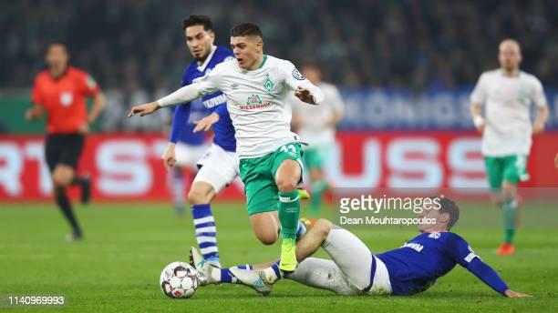 Sebastian Rudy and Suat Serdar tackle Milot Rashica of Werder Bremen during the DFB Cup match between FC Schalke 04 and Werder Bremen at VeltinsArena...