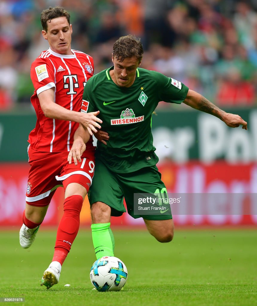 Sebastian Rudy of Bayern Muenchen (l) fights for the ball with Max Kruse of Bremen during the Bundesliga match between SV Werder Bremen and FC Bayern Muenchen at Weserstadion on August 26, 2017 in Bremen, Germany.