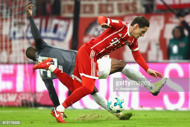 Sebastian Rudy of FC Bayern Muenchen battles for the ball with Kevin Danso of FC Augsburg during the Bundesliga match between FC Bayern Muenchen and...