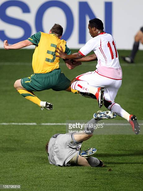 Sebastian Ryall of Australia and Ahmed Khalil Sebait Mubarak Aljunaibi of the UAE jumps over Australian goal keeper Andrew Redmayne during the third...