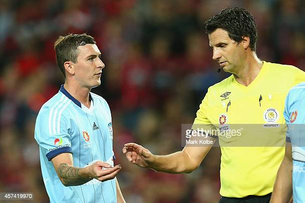 Sebastian Ryall of Sydney FC hands referee Kris GriffithsJones a coin thrown onto the field from the Wanderers fans end during the round two ALeague...