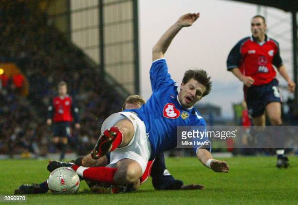 Sebastian Schemmel of Portsmouth is tackled by Kevin Sharp of Scunthorpe during the FA Cup Fourth Round match between Portsmouth and Scunthorpe...