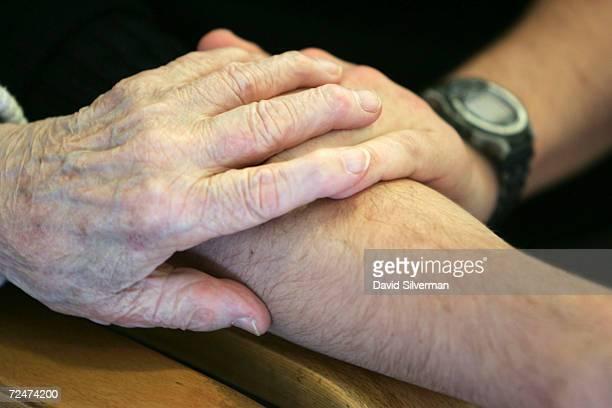 Sebastian Schirrmeister a 20yearold German volunteer from Berlin holds hands with elderly Jewish Holocaust survivor Yanina Brunitzky as he sits and...
