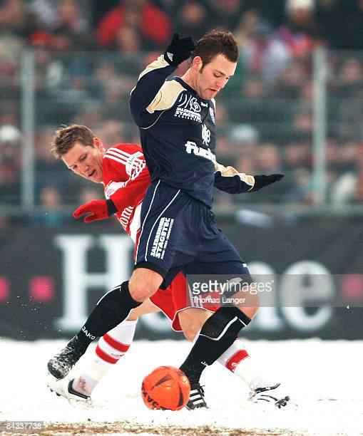 Sebastian Schweinsteiger of Munich and Peter Heyer of Bamberg battle for the ball during the friendly match between FC Eintracht Bamberg and FC...