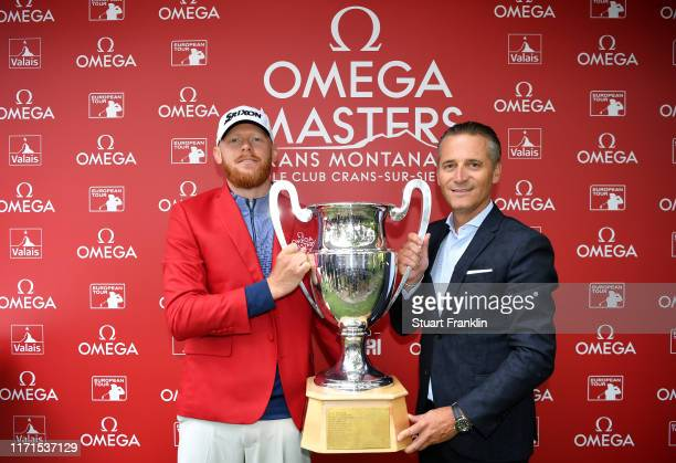 Sebastian Soderberg of Sweden is presented with the trophy by Raynald Aeschlimann president of Omega following his victory in the play off during Day...