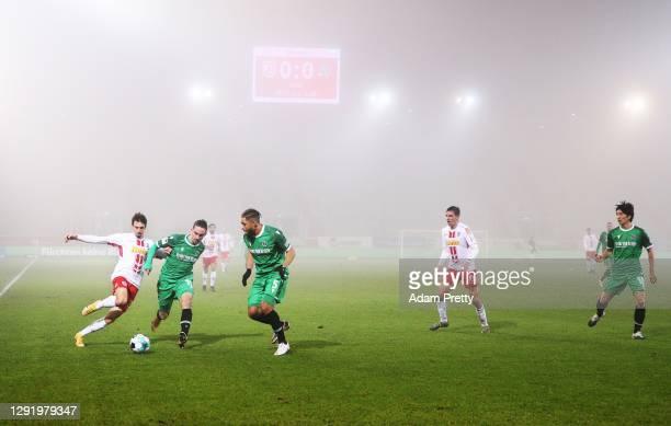 Sebastian Stolze of Jahn Regensburg is challenged by Valmir Sulejmani of Hannover 96 during the Second Bundesliga match between SSV Jahn Regensburg...