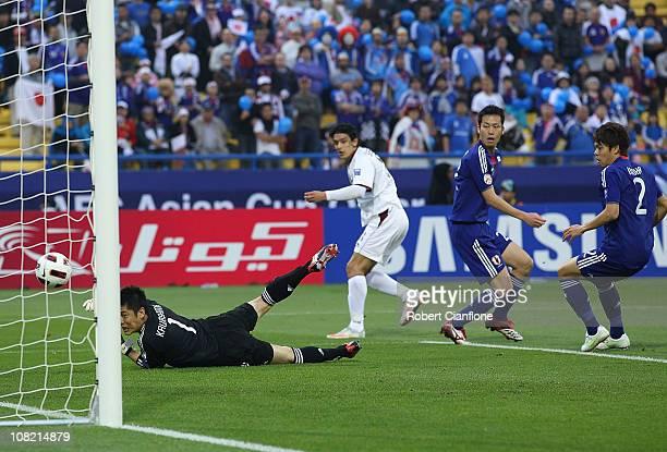 Sebastian Suria of Qatar gets his shot past Japanese goalkeeper Eiji Kawashima during the AFC Asian Cup quarter final match between Japan and Qatar...