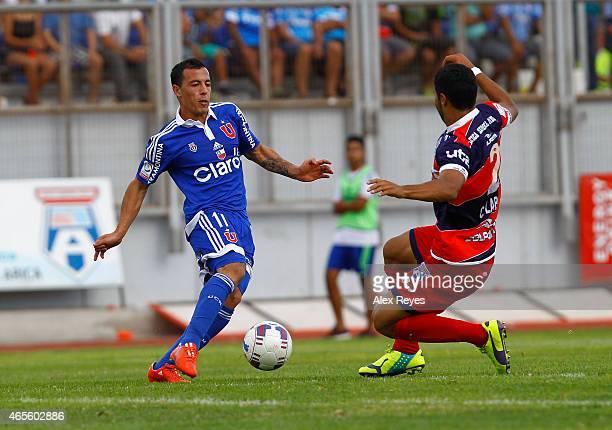 Sebastian Ubilla of U de Chile fights for the ball with Carlos Labrín of San Marcos de Arica during a match between San Marcos de Arica and U de...