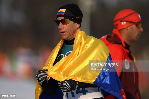 Sebastian Uprimny of Colombia holds his countries flag after crossing the finish line during the CrossCountry Skiing Men's 15km Free at Alpensia...