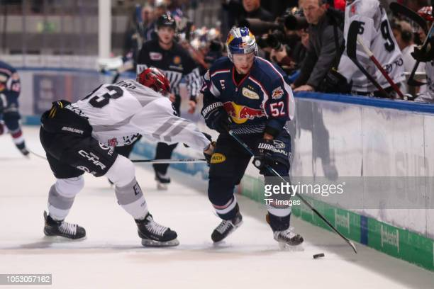Sebastian Uvira of Koelner Haie and Patrick Hager of Red Bull Muenchen battle for the ball during the German Ice Hockey match between EHC Red Bull...