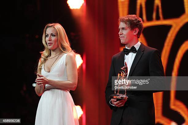 Sebastian Vettel and Andrea Kaiser are seen on stage during the Bambi Awards 2014 show on November 13, 2014 in Berlin, Germany.