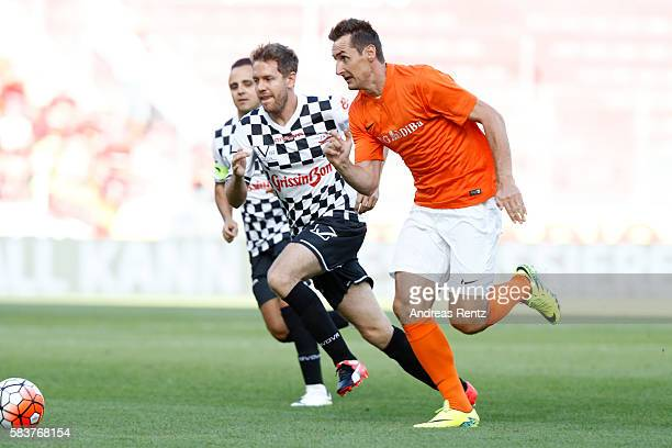 Sebastian Vettel and Miroslav Klose compete for the ball during the 'Champions for charity' football match between Nowitzki All Stars and Nazionale...