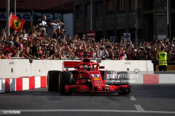 Sebastian Vettel, German racing driver of Scuderia Ferrari racing team, drives his race car in the streets of the city during the Formula 1 Milan...