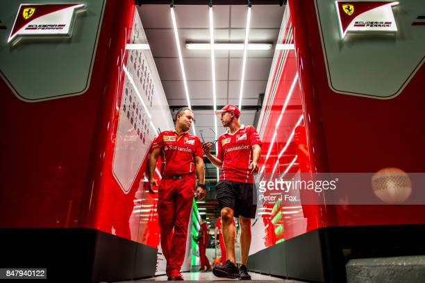 Sebastian Vettel of Ferrari and Germany with a Ferrari team memberduring qualifying for the Formula One Grand Prix of Singapore at Marina Bay Street...