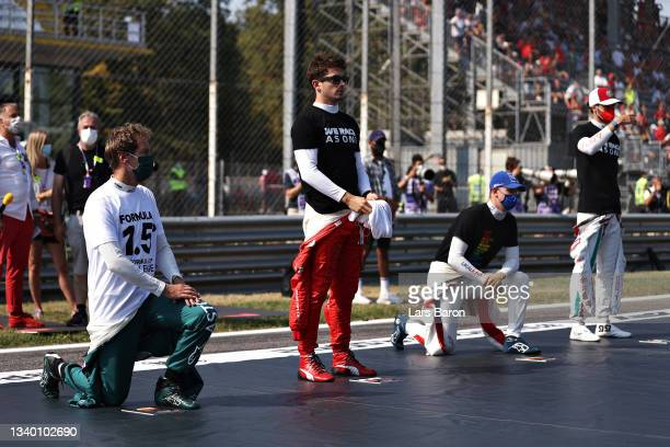 Sebastian Vettel of Germany and Aston Martin F1 Team and Mick Schumacher of Germany and Haas F1 kneel as Charles Leclerc of Monaco and Ferrari and...