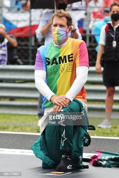 Sebastian Vettel of Germany and Aston Martin F1 Team takes a knee on the grid as part of the We Race As One gesture before the F1 Grand Prix of...