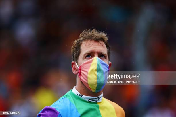 Sebastian Vettel of Germany and Aston Martin wears a rainbow coloured t-shirt and face mask as he looks on from the grid before the F1 Grand Prix of...