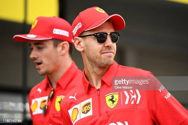 Sebastian Vettel of Germany and Ferrari and Charles Leclerc of Monaco and Ferrari walk in the Pitlane during previews ahead of the F1 Grand Prix of...