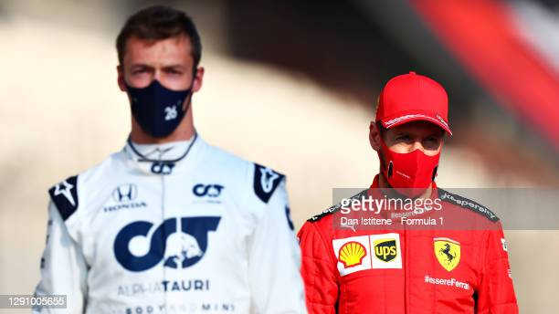 Sebastian Vettel of Germany and Ferrari and Daniil Kvyat of Russia and Scuderia AlphaTauri look on as they stand on the grid prior to the F1 Grand...