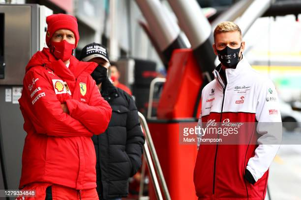 Sebastian Vettel of Germany and Ferrari and Mick Schumacher of Germany and Alfa Romeo Racing talk in the Pitlane during a weather delayed FP2 during...